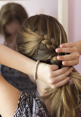 Teenage girl adjusts her hair, hair weaves