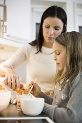 Mother and daughter adding flavor in cup at kitchen