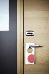 Label hanging on door handle in hotel