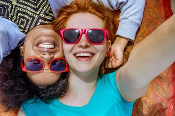 smiling girls multi-cultural best friends lying down take selfie photo wearing eyewear