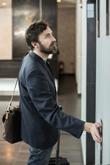 Businessman pushing button of elevator at hotel
