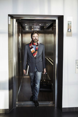 Businessman coming out from elevator in hotel