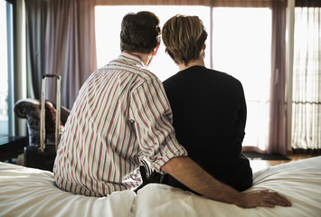 Rear view of couple sitting on bed in hotel room