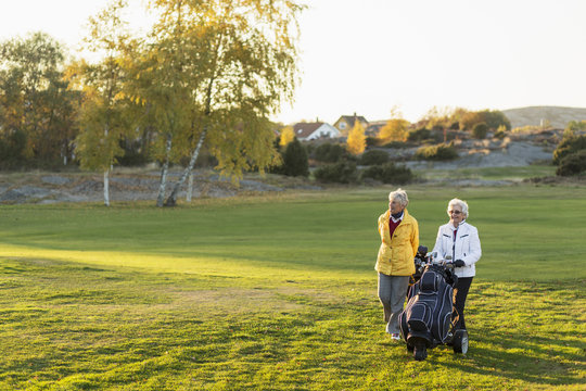 Two senior women walking in golf course