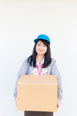 Smiling asian woman in uniform clothes with parcel box on white