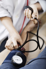 Cropped image of female doctor taking patient's blood pressure at clinic