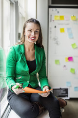 Portrait of businesswoman with document sitting on window sill in creative office