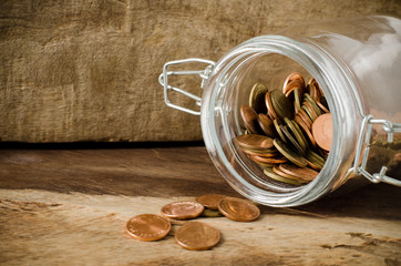 Coins in the bottle on wooden background,saving money concept