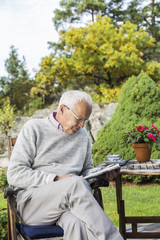 Senior man reading newspaper in yard