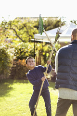 Playful father and son fighting with rakes at garden