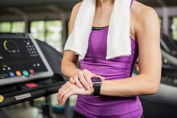Woman using smart watch on treadmill
