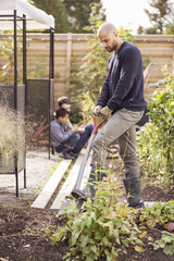 Man digging in garden with children in background