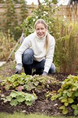 Smiling mature woman gardening at yard
