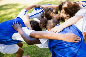 Overhead view of soccer team forming huddle