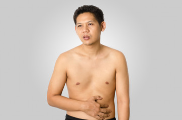 Asia man has stomachache,isolated on gray background