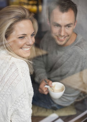 Smiling couple looking out of window while having coffee