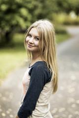 Portrait of smiling teenage girl standing on street
