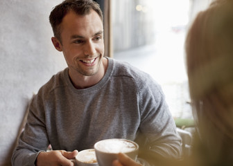 Young man having coffee with woman at cafe