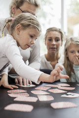 Girl playing card puzzle game with family at home