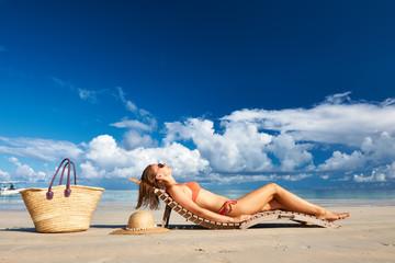 Woman in bikini lying on beach at Seychelles