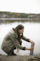 Side view of woman opening thermos at lakeshore
