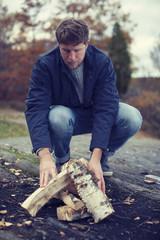 Full length of man arranging wood for bonfire