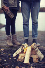 Low section of couple standing by bonfire