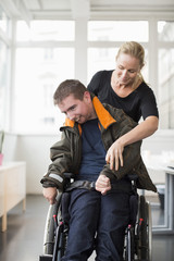 Female caretaker assisting disabled man on wheelchair at home