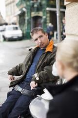 Disabled man with female caretaker at sidewalk cafe
