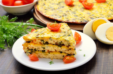 Homemade omelet with herbs and vegetables on wooden background,