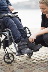 Female caretaker putting on disabled man's shoes outdoors
