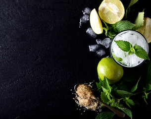 Ingredients for making mojitos (ice cubes, mint leaves, sugar and lime on dark rustic background)
