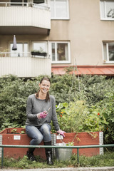 Full length portrait of happy woman with gardening equipment in garden