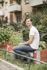 Full length portrait of young man with gardening equipment sitting in garden
