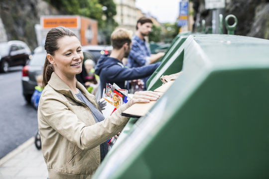 Woman and friends putting recyclable materials into recycling bins