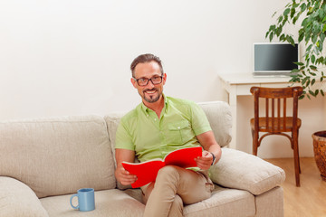 Portrait of handsome man in glasses looking at documents while sitting on sofa or couch. Happy man looking at camera while working from home.