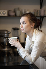 Thoughtful woman with coffee cup looking away while leaning on kitchen counter