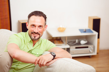 Closeup portrait of handsome man resting and relaxing on sofa or couch at home. Happy man smiling and laughing for camera.