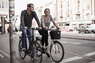 Happy couple riding bicycles on city street