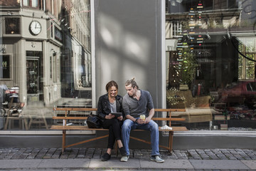 Full length of couple using digital tablet together on sidewalk bench