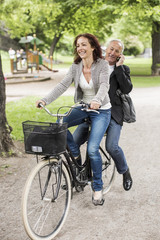 Happy businesswoman riding bicycle while colleague using mobile phone on back seat