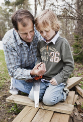 Two generation males with saw and wooden planks in yard