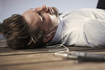 Businessman listening music through mobile phone while lying on boardwalk