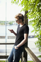 Young man using mobile phone at balcony