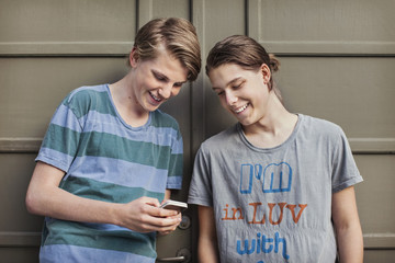 Happy male friends using mobile phone together against wall