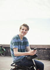 Young man with mobile phone looking away while sitting on bicycle