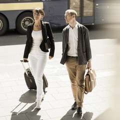 Business people with luggage walking on street