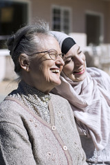 Smiling senior woman and female home caregiver in front of house