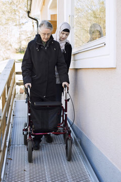 Female home caregiver helping senior woman with walking frame through passage