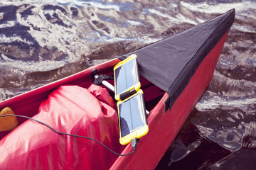 Solar cell phone charger on canoe in lake